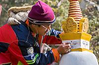 Nepal, Kathmandu, Swayambhunath.  Artist Painting All-seeing Eyes of the Buddha on Miniature Stupas Decorating the Wall around the Stupa.