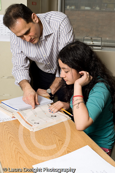Public Middle School Grade 7 mathematics class male teacher working with female student vertical