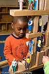 Education preschool 4 year olds block area boy at work playing with human and animal figures on top of a large wooden block structure vertical