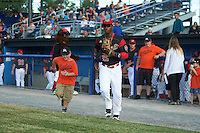 Batavia Muckdogs shortstop Samuel Castro (25) runs out to the field with a young fan before a game against the West Virginia Black Bears on June 29, 2016 at Dwyer Stadium in Batavia, New York.  West Virginia defeated Batavia 9-4.  (Mike Janes/Four Seam Images)