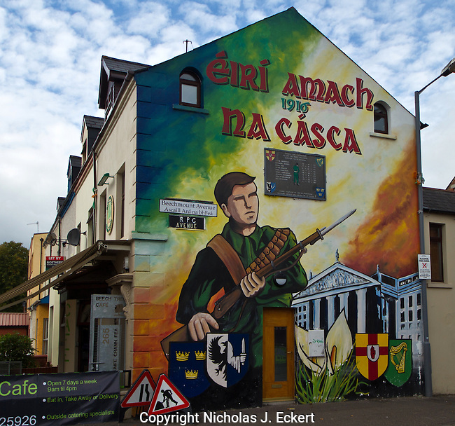 """This mural commemorates the 1916 Easter Rising (which was a fiasco for Irish Republicans but eventually touched off their semi-successful War of Independence).  The building in the background is the General Post Office in Dublin (scene of some of the fiercest fighting of the Rising).  The four shields are the symbols of the four ancient provinces of Ireland...The gaelic words at top translate to """"Easter Rising."""""""