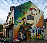 "This mural commemorates the 1916 Easter Rising (which was a fiasco for Irish Republicans but eventually touched off their semi-successful War of Independence).  The building in the background is the General Post Office in Dublin (scene of some of the fiercest fighting of the Rising).  The four shields are the symbols of the four ancient provinces of Ireland...The gaelic words at top translate to ""Easter Rising."""