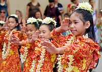 Young girls wearing yellow plumeria lei perform hula at Ward Warehouse shopping center in Honolulu, O'ahu