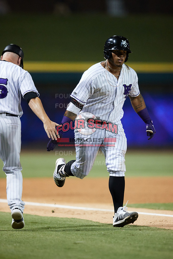 Harvin Mendoza (17) of the Winston-Salem Dash skaps hands with third base coach Ryan Newman (5) after hitting a home run against the Bowling Green Hot Rods at Truist Stadium on September 7, 2021 in Winston-Salem, North Carolina. (Brian Westerholt/Four Seam Images)