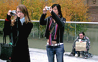 Students taking photos and a homeless man begging outside the Tate Modern, London.