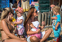 """A young woman breastfeeding her baby while sunbathing on the beach with a friend, and talking to their older children. The baby is feeding while sitting on its mother's lap. Another child is holding a drinking bottle.<br /> <br /> Image from the breastfeeding collection of the """"We Do It In Public"""" documentary photography picture library project: <br />  www.breastfeedinginpublic.co.uk<br /> <br /> <br /> Hampshire, England, UK<br /> 03 /09/2013<br /> <br /> © Paul Carter / wdiip.co.uk"""