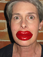 A woman playfully wears red wax lips as they vamp for the camera.