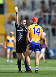 John Conlon of Clare gets a yellow card from referee Fergal Horgan during their All-Ireland quarter final at Pairc Ui Chaoimh. Photograph by John Kelly.
