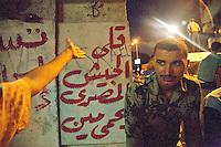 EGITTO, IL CAIRO 9/10 settembre 2011: assalto all'ambasciata israeliana. Migliaia di manifestanti egiziani, ancora infuriati per l'uccisione di cinque guardie di frontiera egiziane da parte dell'esercito israeliano, hanno fatto irruzione nella sede diplomatica israeliana e sono stati poi sgomberati da esercito e polizia egiziana. Nell'immagine: il braccio di un manifestante sotto lo sguardo di un poliziotto egiziano.<br /> Egypt attack to the Israeli embassy  Attaque à l'ambassade israelienne Caire