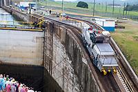 "Panama Canal, Panama.  Entering First Lock, Caribbean Side, Heading toward Lake Gatun.  ""Mule"" Locomotive Pulling Ship Forward into the Lock While Passengers Watch on Deck."