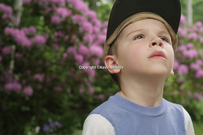 Boy with a cap on in a garden looking up.