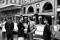 """""""Portai [Portay], Picard, Me Cathala, Me Bouscatel, Me Rastoul"""". Place Wilson. 30 novembre 1976. plan 3/4 de profil de Christian Portay (un des accusés) discutant avec son avocat Me Cathala, deux policiers les entourent ; en arrière-plan entrée du restaurant """"Le Lafayette"""". Cliché pris le jour d'une reconstitution judiciaire dans le cadre de l'affaire du meurtre de René Trouvé. Observation: Affaire René Trouvé-Birague : le 19 février 1976, le journaliste René Trouvé est assassiné d'une balle dans la tête, par deux inconnus, alors qu'il regagne son domicile au 33 rue Bayard."""