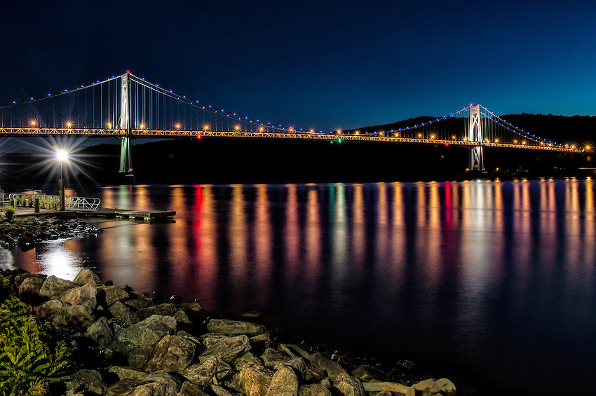 """A waterfront view of the Mid-Hudson Bridge, Poughkeepsie, NY, in the evening after sunset, during the """"blue hour."""""""