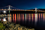 "A waterfront view of the Mid-Hudson Bridge, Poughkeepsie, NY, in the evening after sunset, during the ""blue hour."""