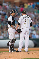 Charlotte Knights catcher Kevan Smith (32) has a meeting on the mound with starting pitcher Kyle Drabek (31) during the game against the Indianapolis Indians at BB&T BallPark on June 20, 2015 in Charlotte, North Carolina.  The Knights defeated the Indians 6-5 in 12 innings.  (Brian Westerholt/Four Seam Images)