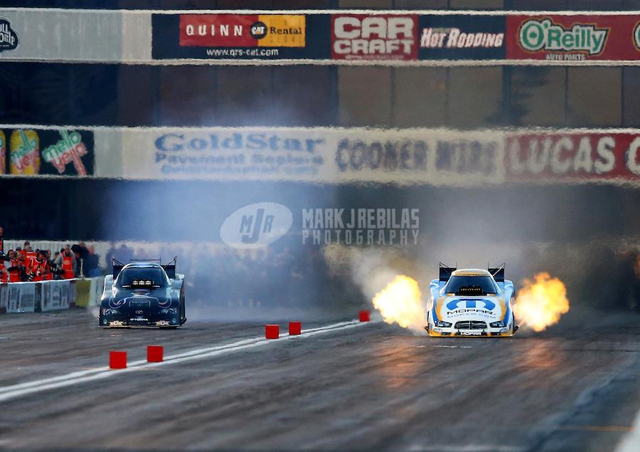 Feb 8, 2014; Pomona, CA, USA; NHRA funny car driver Matt Hagan (right) races alongside Alexis DeJoria during qualifying for the Winternationals at Auto Club Raceway at Pomona. Mandatory Credit: Mark J. Rebilas-