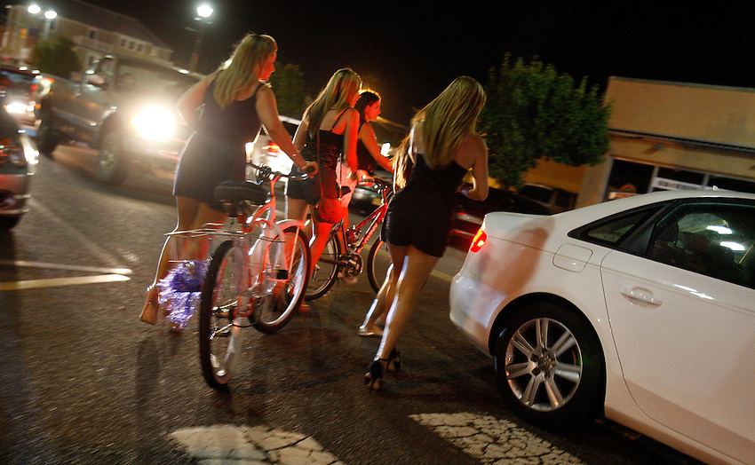 """A group of twenty-something women in high heels walk their bicycles across the Boulevard as they leave the """"Jersey Shore' house of MTV fame to go clubbing on an early Sunday morning in Seaside Heights. SEASIDE HEIGHTS, NJ  (8/18/2010)"""