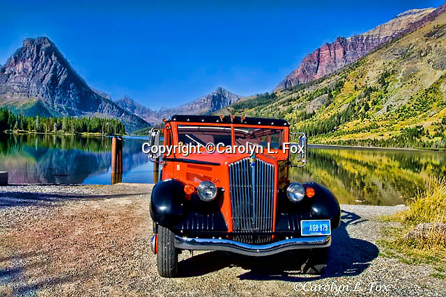 The Glacier Touring Car sits next to a lake in Glacier National Park.