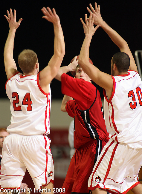VERMILLION, SD - JANUARY 24:  Dylan Grimsley #24 and Tyler Cain #30 of the University of South Dakota trap Justin Petersen #40 of the University of Nebraska Omaha in the first half of their North Central Conference Game Thursday night at the DakotaDome in Vermillion. (Photo by Dave Eggen/Inertia)
