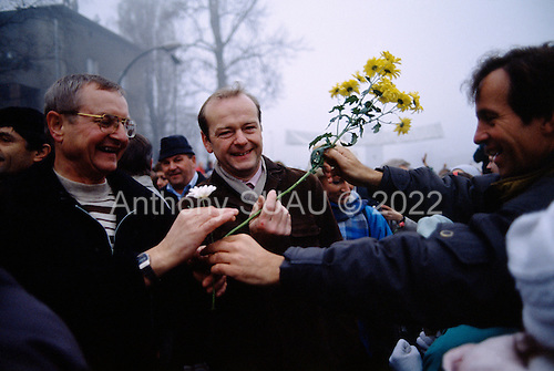 Lichterfelde, Berlin (West) and Teltow, Potsdam (East) crossing post, West Germany<br /> November 14, 1989 <br />  <br /> East and West Germans greet each other with flowers as they cross the border near the Berlin Wall. Germans gathered as the wall is dismantled and the East German government lifts travel and emigration restrictions to the West on November 9, 1989.