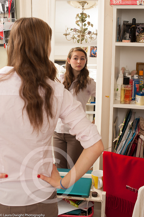 Teenage girl looking at herself in the mirror