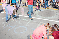 """People use sidewalk chalk to write """"No forced shots"""" on the street as people gather outside the Massachusetts State House for the No Mandatory Flu Shot MA demonstration in Boston, Massachusetts, on Sun., Aug. 30, 2020. The protest was organized in opposition to a newly-enacted law requiring most children in Massachusetts to receive flu vaccines this year as part of public health efforts during the ongoing Coronavirus (COVID-19) global pandemic. Some of those involved in this protest have been involved in the right-wing pro-Trump, pro-reopening protests organized by Super Happy Fun America during spring and summer 2020."""