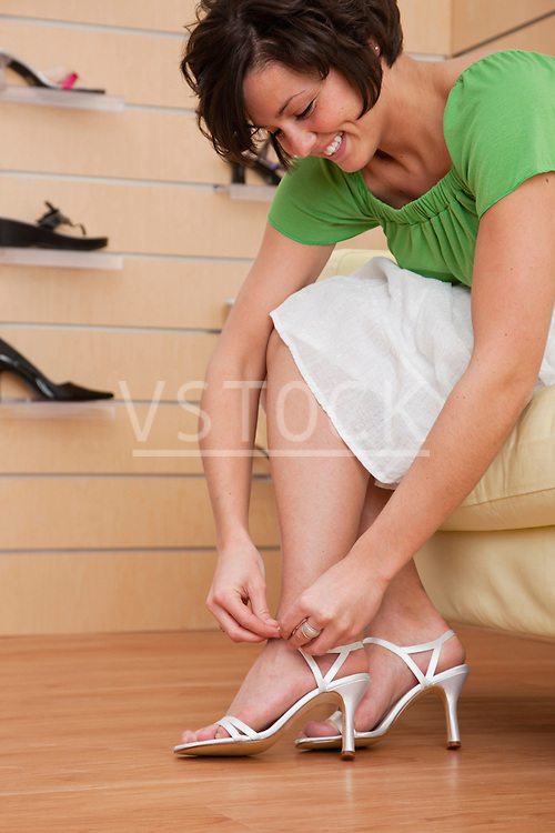 USA, Illinois, Metamora, Young woman trying on high heel shoes in store