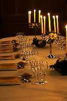 A romantic table set for wine tasting and dinner with many glasses and candelabra, Champagne Ruinart, Reims, Champagne, Marne, Ardennes, France, low light grainy grain