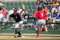 Kannapolis Intimidators first baseman Corey Zangari (14) stretches for a throw as Josh Tobias (5) of the Lakewood BlueClaws hustles down the line at Kannapolis Intimidators Stadium on May 8, 2016 in Kannapolis, North Carolina.  The Intimidators defeated the BlueClaws 3-2.  (Brian Westerholt/Four Seam Images)