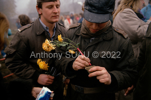 Lichterfelde, Berlin (West) and Teltow, Potsdam (East) crossing post, West Germany<br /> November 14, 1989 <br /> <br /> East German police sign pieces of the Berlin Wall for West Germans after the opening of the Berlin Wall. Germans gathered as the wall is dismantled and the East German government lifts travel and emigration restrictions to the West on November 9, 1989.