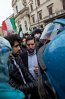 """Protester handcuffed himself.<br /> <br /> Rome, Italy. 12th Apr, 2021. Today, Hospitality Industry workers, Autonomous workers (Partite IVA, VAT Workers), Gym owners, supported by far-right extremist movements and political parties held a demonstration in Piazza San Silvestro, near the Italian Parliament, to highlight the dramatic situation of workers in Italy during the ongoing pandemic Covid-19/Coronavirus, to call for an immediate reopening (The slogan of the demo was: """"Io Apro"""", I Open) of their economic activities, and to call the Italian Government, led by Prof. Mario Draghi, to act for immediate investments, aids (Ristori), and policies to save their industry, and the whole Country. A large number of full riot gears police officers and vehicles, assisted by a water cannons truck and a helicopter were deployed at protection of the Parliament due to a similar violent demo which was held on the 06th of April (1.) in Piazza Montecitorio. The tension between protesters and police officers erupted when a group of protesters tried to force their way to reach the Parliament, full riot gears police officers confronted and pushed them back while glass and plastic bottles, dangerous firecrackers, smoke bombs and flares, placards, were thrown towards the officers. <br /> <br /> Footnotes & Links: <br /> 1. 06.04.2021- Hospitality Demo Outside Italian Parliament Erupts In Violent Clashes With Police https://lucaneve.photoshelter.com/gallery/06-04-2021-Hospitality-Demo-Outside-Italian-Parliament-Erupts-In-Violent-Clashes-With-Police/G0000y2RXXo96Jkk/C0000GPpTqAGd2Gg"""