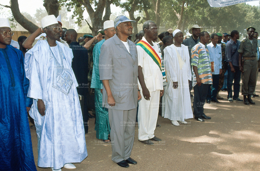 Mali. Province of Segou. Niono. October 16 2003. Worlwide food day. The malian president (blue cap) Amadou Toumani Toure (ATT) and the people's representatives of the area wearing on their clothes the tricolour cockade (the malian flag: green, yellow and red ) greet in a military matter the soldiers. Some men are dressed with western clothes and others wears the traditional malian suit, the Boubou.  © 2003 Didier Ruef
