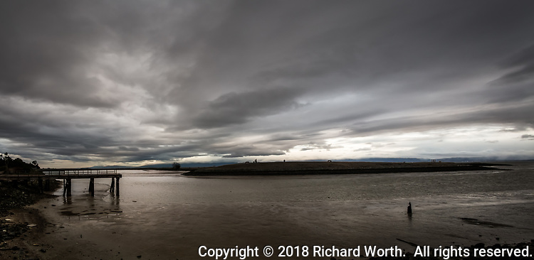 Ominous storm clouds flow over the small boat lagoon and par course jutting into San Francisco Bay, while a derelict pier stands as a reminder of a long gone boat repair operation.  A multi-image panoramic at the San Leandro Marina, San Leandro, California.