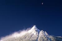 Crescent moon above a windblown, snowy McClellan Butte, Central Cascade Mountains, Washington State.