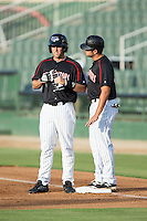 Michael Suiter (left) gets instructions from first base coach Christian Stringer (right) during the game against the Lakewood BlueClaws at Intimidators Stadium on July 16, 2015 in Kannapolis, North Carolina.  The BlueClaws defeated the Intimidators 3-1.  (Brian Westerholt/Four Seam Images)