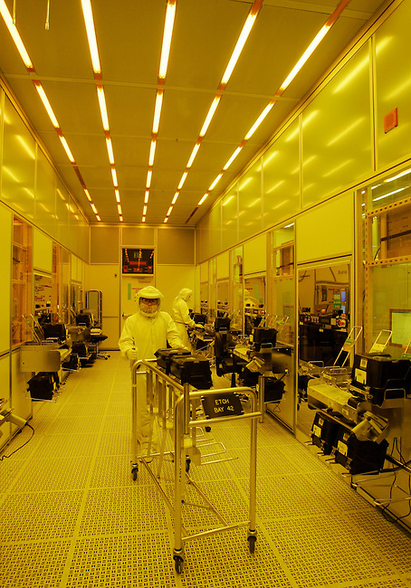 ** FILE **Intel Corp. workers wear clean suits as they work on chip manufacturing in a special light sensitive room at Intel headquarters in a Santa Clara, Calif. file photo from July 17, 2006. Chip-maker Intel Corp. said Tuesday a total of 10,500 jobs will be eliminated over the next year through layoffs, attrition and the sale of underperforming business groups as part of a massive restructuring.  (AP Photo/Paul Sakuma, File)