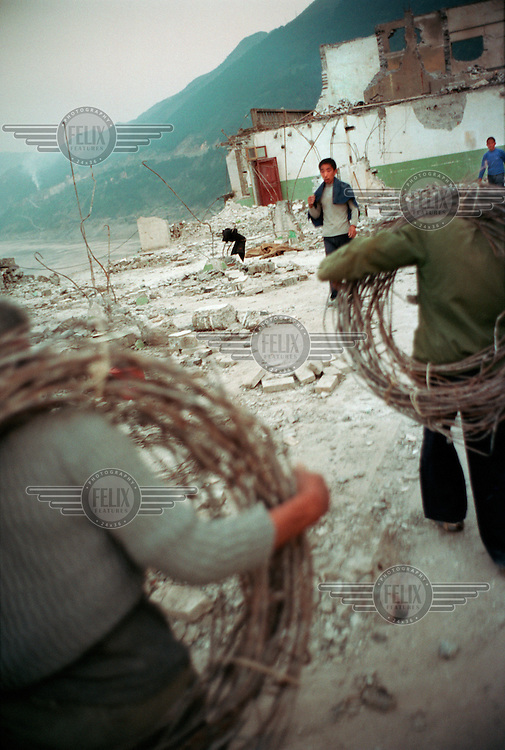 Migrant workers dismantling a recently vacated building. The workers supplement their poor income by selling scrap metal and bricks salvaged from demolition sites. Houses in towns along the Yangtze river are being demolished to make way for the Three Gorges Dam project, which will raise the water levels of the river and inundate lower-lying areas.