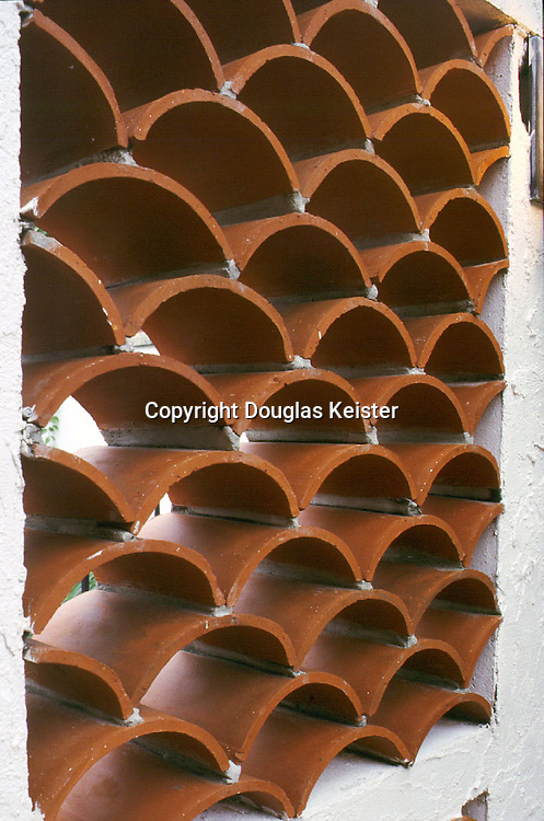Barrel tile had many uses besides merely covering roofs.  In this example, multiple courses of tile are stacked in staggered fashion to produce a gracefully-patterned grille.   Similar techniques were used to produce gable vents and patio screens.  The barrel tile's characteristic half-round shape originally resulted from being formed over the tilemaker's thigh, though most production was already mechanized by the Twenties.