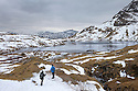 Two hikers looking over Stickle Tarn, Lake District National Park, Cumbria, UK. February.