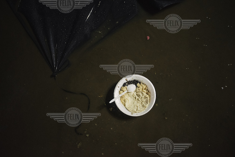 A bowl of food floats on a puddle where Central American Migrants installed their shelter to sleep for a night in the main square of the city.