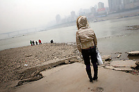 CHINA. Sichuan Province. Chongqing. A woman stands on the banks of the Yangtze river which is at its lowest levels for 150 years as a result of a countrywide drought. Chongqing is a city of over 3,000,000 people, famed for being the capital of China between 1938 and 1946 during World War II. It is situated on the banks of the Yangtze river, China's longest river and the third longest in the world. Originating in Tibet, the river flows for 3,964 miles (6,380km) through central China into the East China Sea at Shanghai.  2008