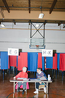 "Ballot inspectors Joyce Soucy (left) and Sandy Russell wait to check in voters as Merrimack Ward 1 Primary Voting begins at James Mastricola Upper Elementary School in Merrimack, New Hampshire, on Tue., Feb. 11, 2020. This is Soucy's first year working on an election. She was recruited by Russell, who has been working on elections ""as soon as I turned 21 [in 1962],"" she said."