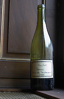 A half empty dusty old bottle with a hand written label saying Louis Jadot Beaune Clos des Couchereaux 1983 Burgundy red wine side-lit side light, closeup on a window sill, Maison Louis Jadot, Beaune Côte Cote d Or Bourgogne Burgundy Burgundian France French Europe European