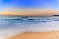 Wave on Gigaro beach during a colorful twilight sunrise on the Mediterranean Sea and the islands in gulf of Saint-Tropez, Azure coast France