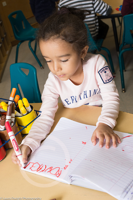 Education Preschool 3-4 year olds classroom scene girl writing her name with marker in notebook