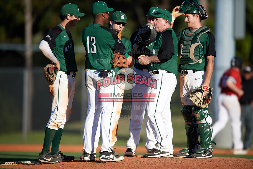 Dartmouth Big Green head coach Bob Whalen (2) talks with (clockwise) third baseman Blake Crossing (13), shortstop Nate Ostmo (5), second baseman Sean Sullivan (4), first baseman Michael Calamari (3), and catcher Bennett McCaskill (18) while making a pitching change during a game against the Northeastern Huskies on March 3, 2018 at North Charlotte Regional Park in Port Charlotte, Florida.  Northeastern defeated Dartmouth 10-8.  (Mike Janes/Four Seam Images)