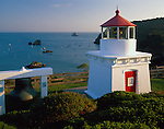 Humbolt County, CA<br /> Trinidad Memorial Lighthouse stands above small boats harbored in Trinidad Bay