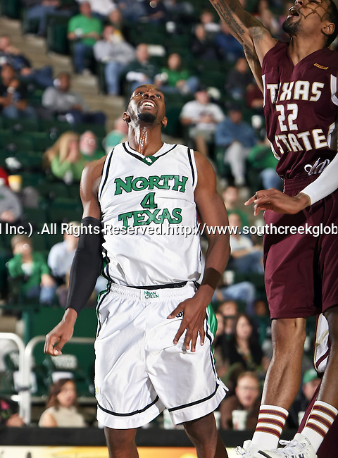 North Texas Mean Green forward George Odufuwa (4) watches as Texas State Bobcats forward Tony Bishop (22) makes a lay up in the game between the Texas State Bobcats and the University of North Texas Mean Green at the North Texas Coliseum,the Super Pit, in Denton, Texas. UNT defeated Texas State 85 to 62