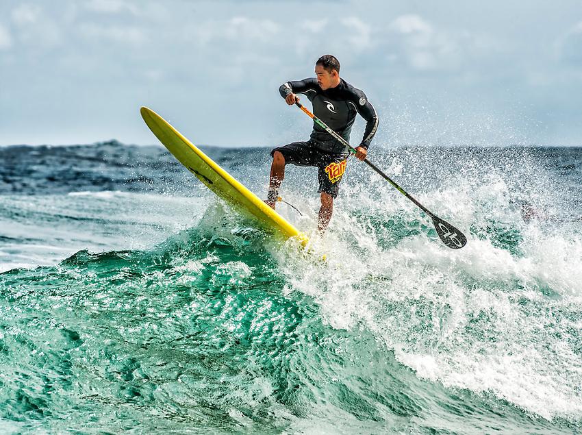 A paddle surfer balances on a wave at Kealia Beach, on the eastern shore of Kauai.