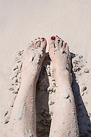 Woman's feet and legs covered with sand.